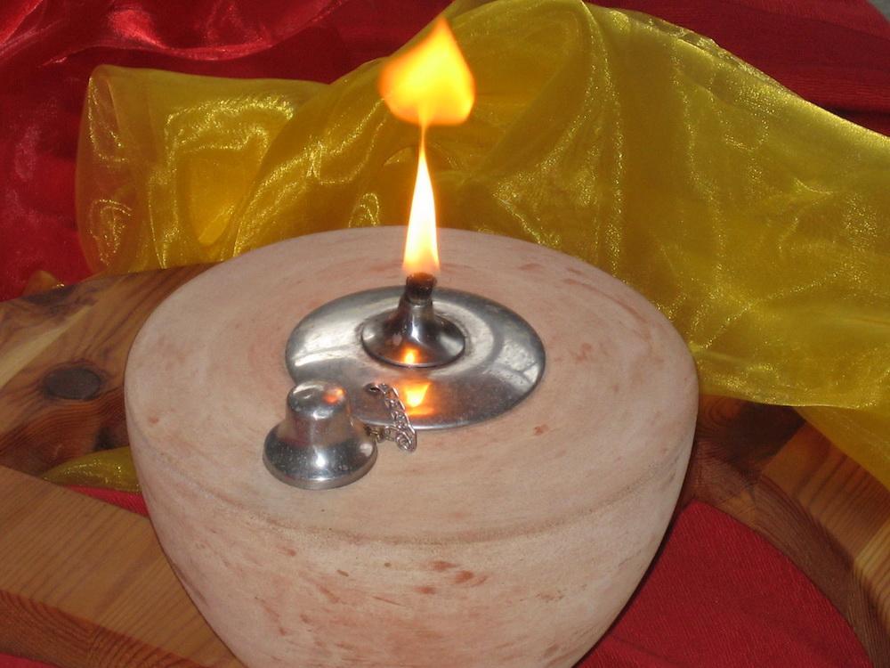Öllampe aus Keramik mit Flamme, umgeben von roten und gelben Stoffen